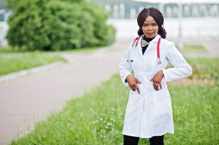 Young african american female doctor in white coat with a stethoscope posed outdoor.