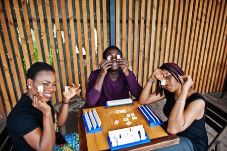 Group of three african american friends play table games. Foto de archivo
