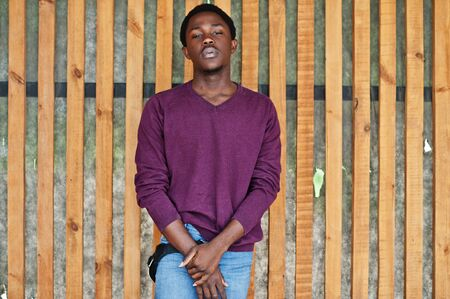 Young african american man in violet jumper posed against wooden wall. Imagens