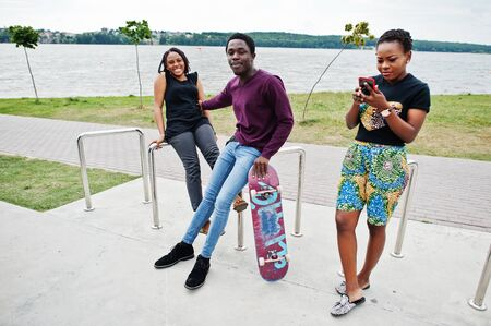 Group of three african american friends with skateboard.