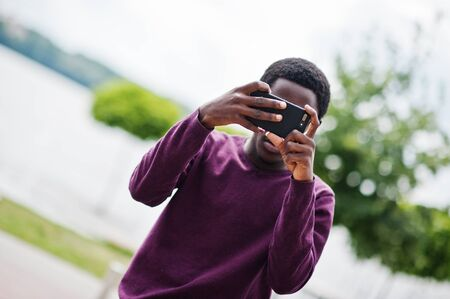 African american man making photo on his mobile phone.