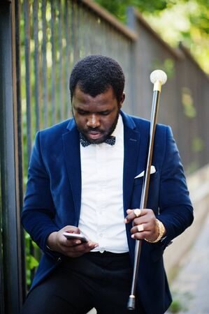 Handsome fashionable african american man in formal wear and bow tie with walking stick looking at mobile phone.