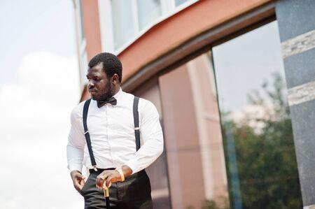 Schöner modischer afroamerikanischer Mann in formeller Kleidung, Fliege und Hosenträgern, Gehstock. Standard-Bild