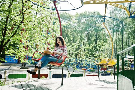 Portrait of brunette girl in pink glasses and hat with ice cream at amusement park. Imagens