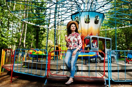 Brunette girl with ice cream in the amusement park.