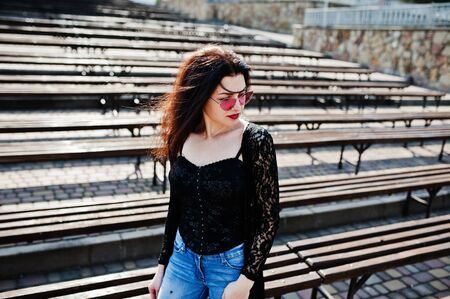 Brunette girl in pink glasses wear on black posed outdoor on sunny day against row of benches.
