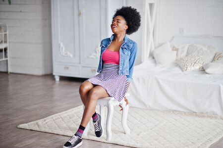 Attractive african american woman with afro hair wear on skirt and jeans jacket, posed at white room. Fashionable black model.