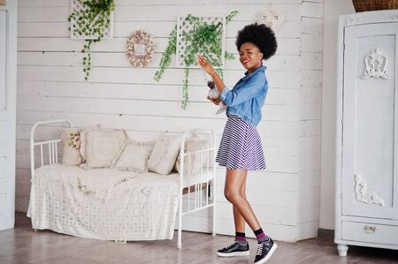 Attractive african american woman with afro hair wear on skirt and jeans jacket, posed at white room. Fashionable black model hold old gasoline lamp.