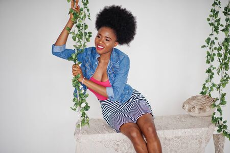 Attractive african american woman with afro hair wear on skirt and jeans jacket, posed at white room on swing. Fashionable black model.