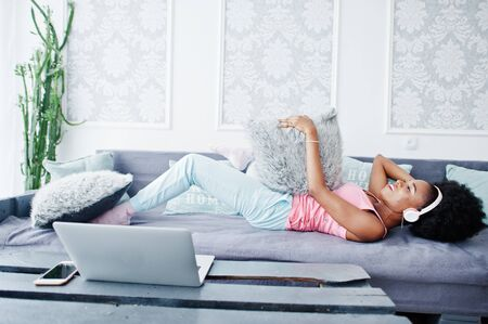 Young african american woman sitting on the couch while working on laptop and listen music on earphones.