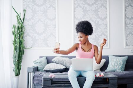 Young african american woman sitting on the couch while working on laptop, streaming video on her phone.