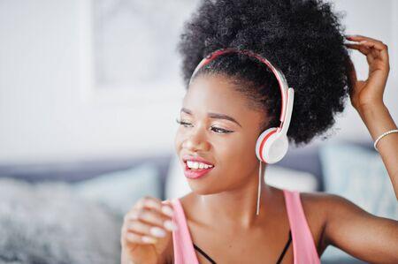 Młoda kobieta african american słuchać muzyki na słuchawkach.