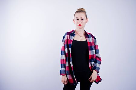 Young woman at checkered shirt posed against white