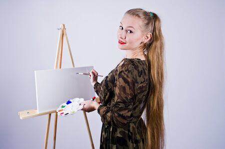Beautiful woman artist painter with brushes and oil canvas posing in studio isolated on white. Stock Photo