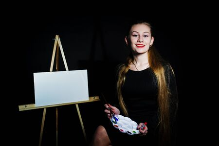 Beautiful woman artist painter with brushes and oil canvas posing in studio isolated on black. Stock Photo