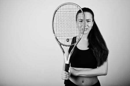 Black and white portrait of beautiful young woman player in sports clothes holding tennis racket while standing against white