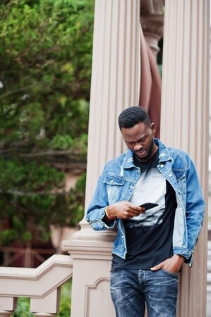 Young attractive serious african american man model. Modern handsome guy in jeans jacket standing on urban city street and looking at his mobile phone.