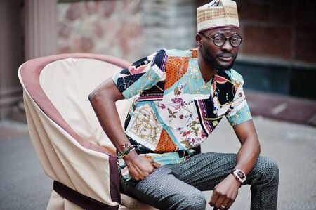 Handsome afro american man wearing traditional clothes, cap and eyeglasses in modern city sitting on chair.