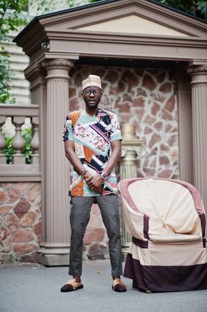 Handsome afro american man wearing traditional clothes, cap and eyeglasses in modern city standing near chair.