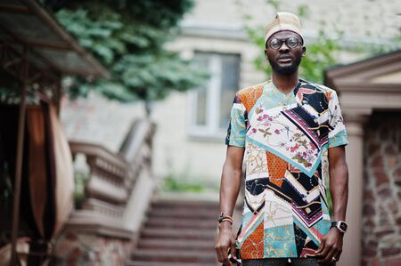 Handsome afro american man wearing traditional clothes, cap and eyeglasses in modern city.