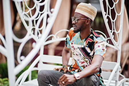 Handsome afro american man wearing traditional clothes, cap and eyeglasses sitting at white carriage.