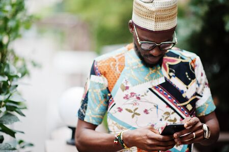 Handsome afro american man wearing traditional clothes, cap and eyeglasses in modern city looking at his cell phone.
