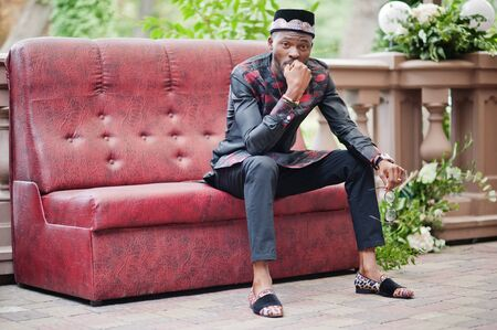Handsome afro american man wearing traditional clothes, cap and eyeglasses in modern city sitting at couch.
