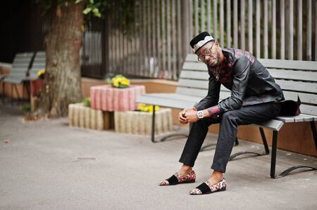 Handsome afro american man wearing traditional clothes, cap and eyeglasses in modern city sitting on bench.