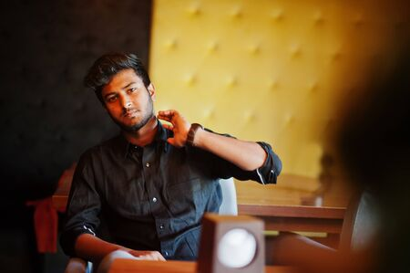 Confident young indian man in black shirt sitting at cafe.