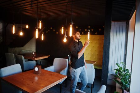 Confident young indian man in black shirt standing at cafe.