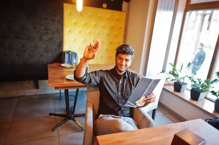 Confident young indian man in black shirt sitting at cafe, read menu and calling waiter.