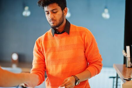 Confident young indian man in orange sweater sitting bar counter at cafe and calculated with the bartender.