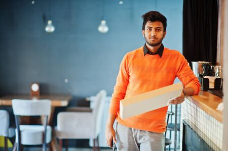 Confident young indian man in orange sweater standing near bar counter at cafe and hold box for delivery with pizza.