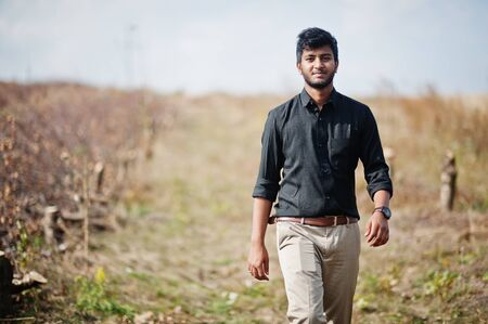 Indian man at black shirt and beige pants posed at field. Reklamní fotografie