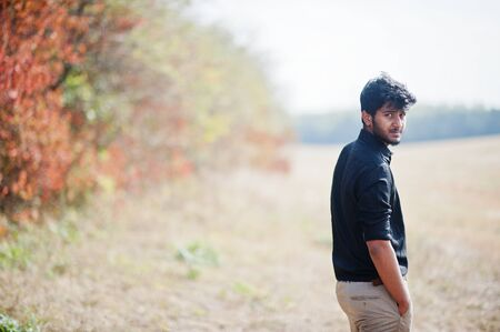 Indian man at black shirt and beige pants posed at field against autumn leaves. Stock Photo