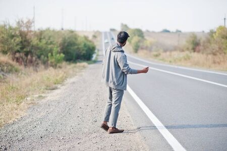 Hitchhiking indian man travelling by hitchhike on road side on highway. Reklamní fotografie