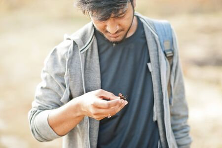 Indian man at casual wear hold butterfly in hand. 스톡 콘텐츠