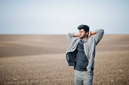Indian man at casual wear posed at field alone. Stock Photo