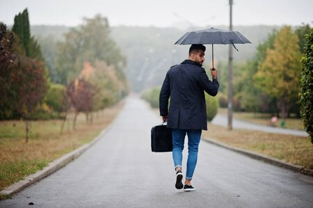 Fashionable tall arab beard man wear on black coat with umbrella and bag case posed at rain weather day.