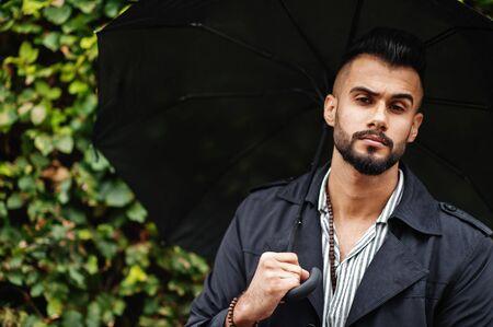 Fashionable tall arab beard man wear on black coat with umbrella posed at rain weather day.