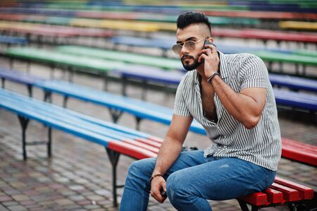 Fashionable tall arab beard man wear on shirt, jeans and sunglasses sitting on colored row of benches and use his phone.