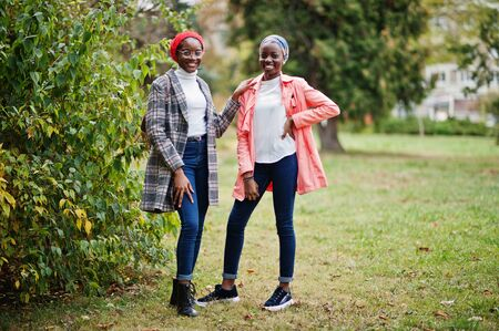 Two young modern fashionable, attractive, tall and slim african muslim womans in hijab or turban head scarf and coat posed at park together. Foto de archivo