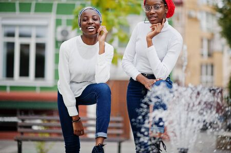 Two young modern fashionable, attractive, tall and slim african muslim womans in hijab or turban head scarf posed together.