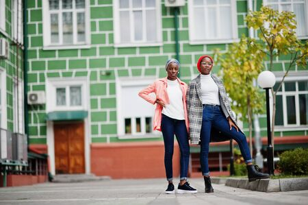 Two young modern fashionable, attractive, tall and slim african muslim womans in hijab or turban head scarf and coat posed.