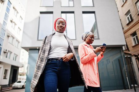Two young modern fashionable, attractive, tall and slim african muslim womans in hijab or turban head scarf and coat posed with mobile phones.