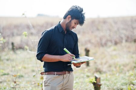 South asian agronomist farmer with clipboard inspecting cut trees in the farm garden. Agriculture production concept. Stock Photo