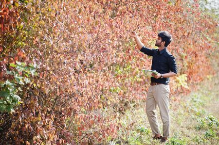 South asian agronomist farmer with clipboard inspecting trees in the farm garden. Agriculture production concept.