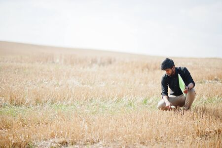 South asian agronomist farmer inspecting wheat field farm. Agriculture production concept.