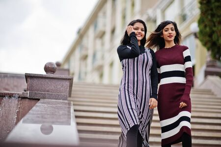 Portrait of two young beautiful indian or south asian teenage girls in dress posed at stairs on city.