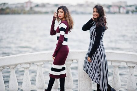 Portrait of two young beautiful indian or south asian teenage girls in dress at bridge of river.